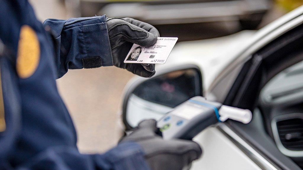 Polis inspekterar ett körkort och håller en alkomätare i andra handen.