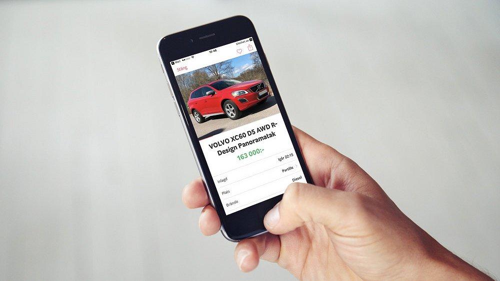 Person håller i mobiltelefon som visar en begagnad Volvo XC60 på Blocket